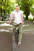 Mature man cycling at park — Stock Photo