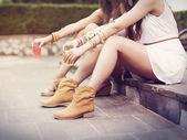Hippie women sitting on curb — Stock Photo