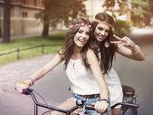 Boho girls on the tandem bicycle — Stock Photo