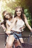 Boho girls riding a bike — Stock Photo