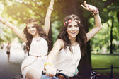 Hippie girls on bike — Stock Photo