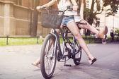 Boho girls legs during riding tandem bike — Stock Photo