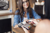 Smiling woman paying for coffee — Stock Photo