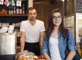 Smiling waiter and beautiful female customer — Stock Photo