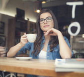 Woman drinking coffee at cafe — Stock Photo