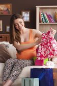 Pregnant woman looking on new dress for little girl — Stock fotografie