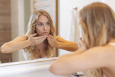 Woman removing pimple from her face — Stock Photo