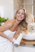 Blonde woman drying hair — Stock Photo