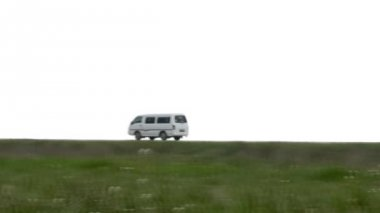 White van quickly goes on the steppe highway against the backdrop of cloudy skies and behind the hill