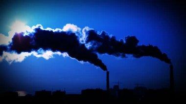 Fumar fora de tubos de planta. fundo do céu azul escuro. — Vídeo Stock
