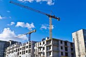 Building crane on the background of blue sky and of the house under construction — Stock Photo