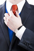Business Man Adjusting Orange Necktie — Stock Photo