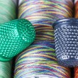 Stock Photo: Spools and Metallic Thimbles. Colored Texture Macro.