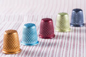 Colored Metallic Thimbles on Fabric — Stock Photo