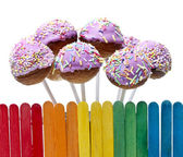 Wooden fence in rainbow colors and pink cake pops — 图库照片