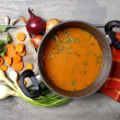 Top view on pot of tomato soup and fresh vegetables on old woode — Stock Photo #23970223