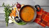 Bovenaanzicht op pot van tomatensoep en verse groenten op oude woode — Stockfoto
