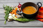 Top view on pot of tomato soup and fresh vegetables on old woode — Stock Photo
