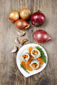 Pickled herring rolls with vegetables on wooden table — Zdjęcie stockowe