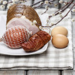 Stock Photo: Smoked ham on squared napkin, on wooden table.