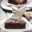 Chocolate cake on white plate, on hessian. Coffee beans on woode — Stock Photo #24885825