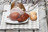 Smoked ham on squared napkin, on wooden table. — Stock Photo