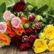 Fabulous bouquet of colorful roses on wooden tray in fresh sprin — Stock Photo