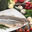 Two raw, fresh rainbow trouts among vegetables. — Stock Photo #24947835