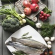 Two raw, fresh rainbow trouts among vegetables.  — Stock Photo