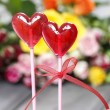 Royalty-Free Stock Photo: Lollipops in heart shape on background of colorful roses