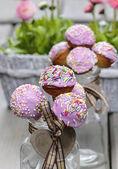 Cake pops dekorerade med strössel på grå träbord. — Stockfoto