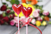 Lollipops in heart shape on background of colorful roses — Stock Photo