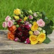 Fabulous bouquet of colorful roses on wooden tray in fresh sprin - Foto de Stock
