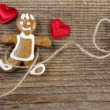 Gingerbread man and cute red hearts on wooden background. — Stock Photo