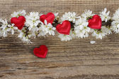 Small red hearts among cherry blossom on wooden background — 图库照片