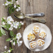 Top view of tiny cakes on wooden background, springtime set. — Stock Photo