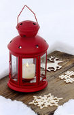 Red lantern standing on wooden board, on snow — Stock Photo