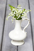 Lilly of the valley flowers in white rustic vase on grey wooden — Stock Photo