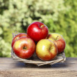 Wicker basket of fresh red ripe apples — Stock Photo