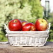 Basket of red ripe apples on a wooden table in the garden. — Stock Photo
