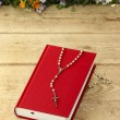 Stock Photo: New red Holy Bible and white rosary on old wooden surface.