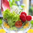 Glass goblet of fresh salad made of fruits and vegetables. - Stock Photo