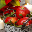 Silver bucket of red ripe apples among candles — Stok fotoğraf