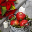 Silver bucket of red ripe apples among candles — Stock Photo