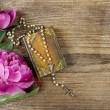 Stock Photo: Pink peony, vintage book and white rosary on wooden background.