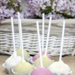 Stock Photo: Pastel colors cake pops on hessian. Wicker basket of lilacs in t