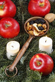 Dried fruits on fir branches among red ripe apples and candles. — Stock Photo