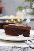 Piece of chocolate cake in white christmas table setting. — Stock Photo