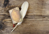 Book and feather on wooden rough background. Copy space. — Stockfoto