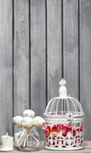 Birdcage with pink flowers inside on rustic wooden background. C — Stock Photo